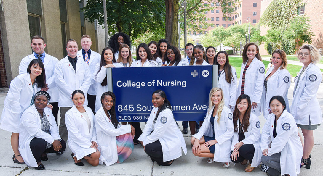 Students pose with College of Nursing sign