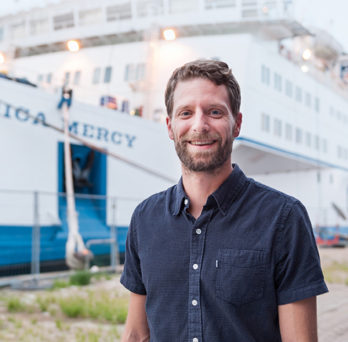 Alumnus Nate Claus standing in front of Africa Mercy ship