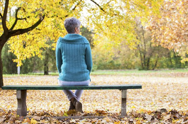 Lonely woman on park bench