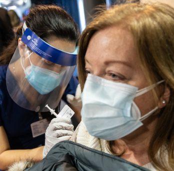 Nursing student Maria Escamilla administering a COVID-19 vaccination